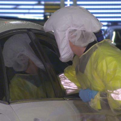 En sjukskötare i gul skyddsutrustning, vit skyddsmössa, ansiktsskydd och visir lutar sig in genom ett sidofönster i en vit bil för att ta ett coronatest på en person.