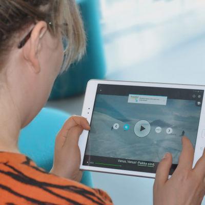 Nainen katsoo Yle Kielikoulua pad-laitteen näytöltä.