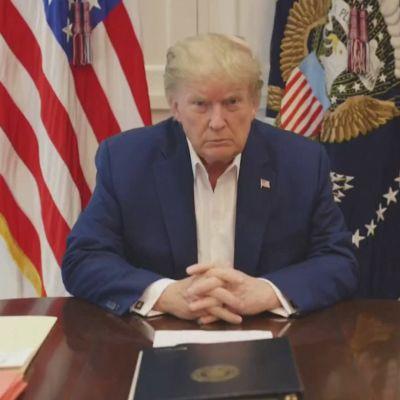 Yhdysvaltain presidentti Donald Trump puhuu sairaalassa pöydän ääressä, ei solmiota, taustalla Yhdysvaltain lippu ja valkoista kaapistoa