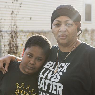 Minneapolislainen Queen poikansa kanssa kodin edustalla.