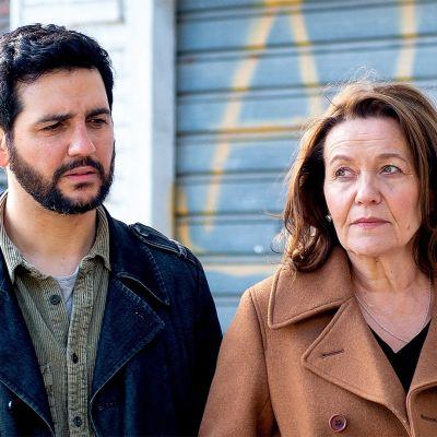 Andres (Fran Perea) & Hilkka (Riitta Havukainen) seisovat kadulla. Seinässä graffiteja.