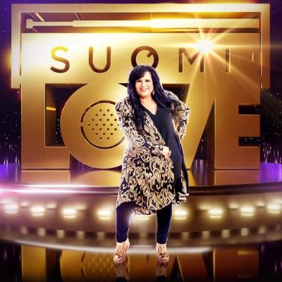 Kaija Koo poseeraa kirjaillussa kulta-musta-takissa SuomiLOVE-logon edessä.