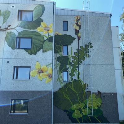 Huittisten kaupungin vuokrakerrostalon seinässä keltaista luonnonkukkaa esittävä valtava maalaus