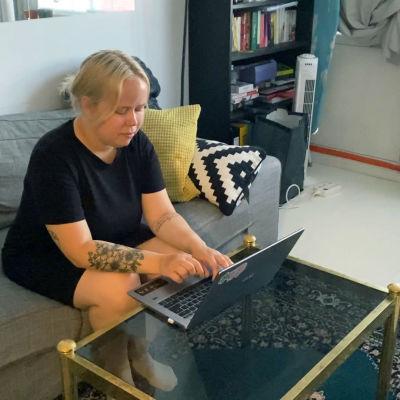 En kvinna med ljust hår och svart tröja sitter i en soffa och jobbar på sin laptop.