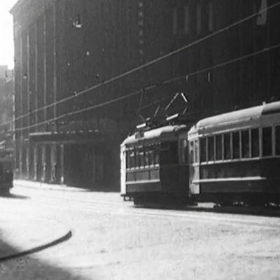Kuvakaappaus lyhytelokuvasta Pääkaupunki aamusta iltaan. Raitiovaunu ajaa auringonpaisteessa.