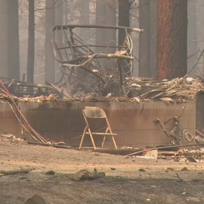 Bild på område i skog som brunnit. På bilden syns en stol och ruiner.