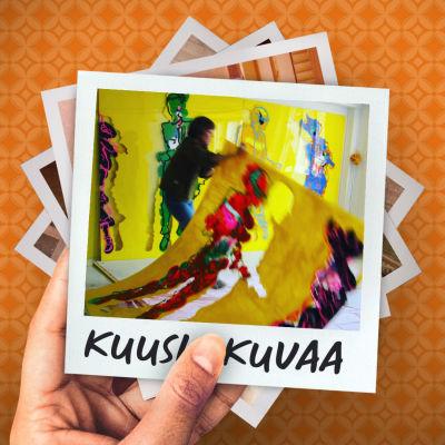 Kirsti Tuokko nostaa suurta keltaista maalausta lattialta.