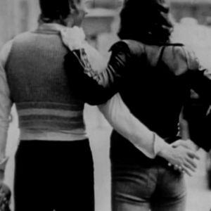 Ett par står hand i hand och regnbågsflaggan i bakgrunden.