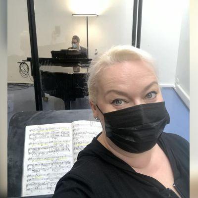 Oopperalaulaja Johanna Rusanen-Kartano mustassa maskissa, taustalla Kansallisoopperan harjoituspianisti Hans-Otto Ehrström.