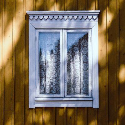 Keltaisen puutalon seinää, valkopokainen ikkuna, ikkunassa pitsiverhot