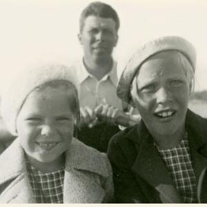Meri Louhos pikkutyttönä soutuveneessä siskonsa ja isänsä kanssa.