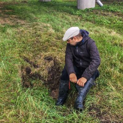 Henrik Kettunen sitter i en grop i marken. Den är en spricka in i ett rör som Hagabäcken forsar under Krämertsskogsvägen igenom.