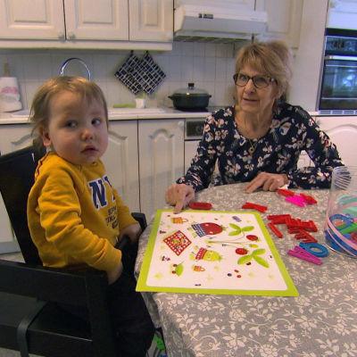 En äldre kvinna sitter vid ett bord med ett barn. De leker med en magnetplatta.