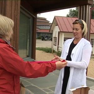 Toimittaja Kati Leskinen antaa Jutta Urpilaiselle pinkit verkkosukkahousut.