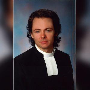 Harri Henttinen papin puvussa valmistujaiskuvassaan.