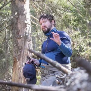 Mies nojaa kaatuneeseen puunrunkoon metsässä.