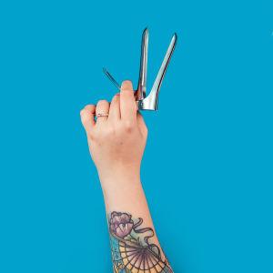 Naisen tatuoitu vasen käsi pitää spekulaa eli ankannokkaa. Instrumentti näyttää hieman aseelta.