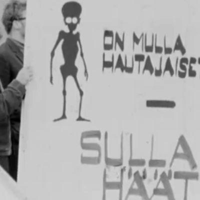 Nälänhätään viittaava juliste mielenosoituksessa Temppeliaukion kirkon vihkiäisissä.