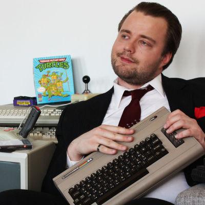 Toimittaja Antti Melkko sliipattuna, pukuun pukeutuneena, vanhan Commodore 64 konsolin kanssa.