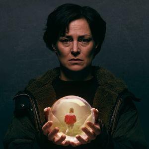 Rita (Lotta Lehtikari) pitelee lasipalloa käsissään synkän näköisenä tummassa kuvassa.