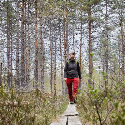 Eräopas Minna Jakosuo retkeilyvaatteissa kävelee pitkospuita kohti kameraa, ympärillä mäntymetsää