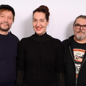 Levylautakunnan vieraina olleet Pauli Hanhiemi, Tuuli Saksala ja Timo Löyvä valkean seinän edessä.