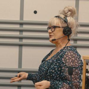 Musiikkitoimittaja Tarja Närhi seisoo radiostudiossa ja juontaa.
