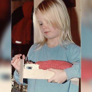 Outi Pyy sinisessä paidassaan noin 4-vuotiaana. Hänellä on kädessään isän tekemä nuken sänky, jossa on pinkki peitto.