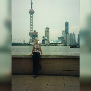 Outi Pyy Shanghaissa. Taustalla näkyy rakennuksia ja vesistöä.