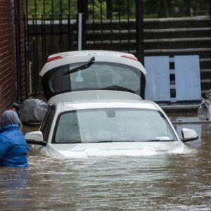 Människa och bil vadar i översvämningar i södra Wales.