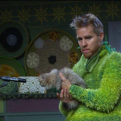 Kusel (Henrik Heselius) från Hittehatt håller i en katt framför en mikrofon
