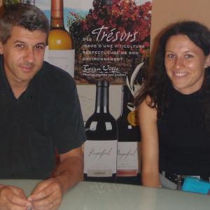Ranskalaiset mies ja nainen istuvat pöydän ääressä ja hymyilevät kameralle.