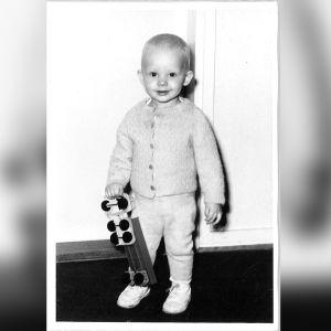 Harri Henttinen noin kaksivuotiaana. Kuva on mustavalkoinen ja Henttisellä on kädessää leikkiauto.