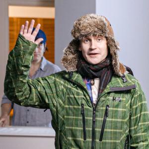 Kuvassa mies heiluttaa kättä karvahattu päässä