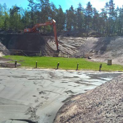En grävmaskin jobbar med sandvallar som omger en gräsplätt och ett gjutet område.