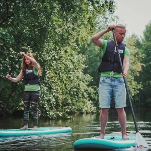 Man och kvinna står på varsin paddelbräda och paddlar i en å.