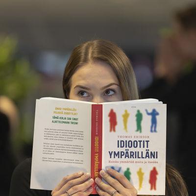 Nainen katsoo kameraan Idiootit ympärilläni -kirjan takaa kyllästynyt ilme kasvoillaan. Takana on himmeällä kaksi muuta hahmoa.