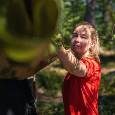 Susan Kröger ripustaa sadesuojaa riippumattonsa päälle.