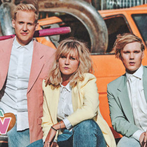"""Simon Karlsson, Märta Westerlund och Kristian Westerling poserar på en avstjälpningsplats med ett skrotigt fordon oi bakgrunden. Pärmbild för musikvideo """"Jag vill ha korv."""""""