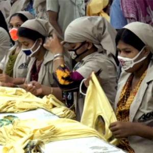 Naiset tekevät paitoja tehtaassa Bangladeshissa.