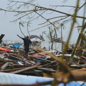 En man går över en massa bråte på Bahamas där orkanen Dorian dragit fram.