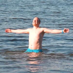 En glad man står i vattnet med badbyxor på sig.
