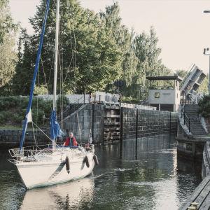 Segelbåt har precis kommit ut ur Vääksy kanal, kanalmynningen i bakgrunden.
