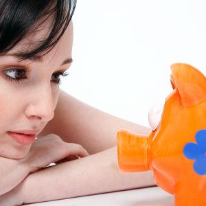 Nainen tuijottaa säästöpossua
