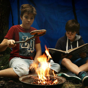 Två pojkar sitter i ett vindskydd och läser/grillar