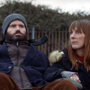 Simon tillsammans med sin fru Ruth vid en parkbänk.