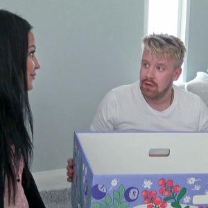 Lassi katsoo Katia ja pitää käsissään äitiyspakkauksen pahvilaatikkoa.