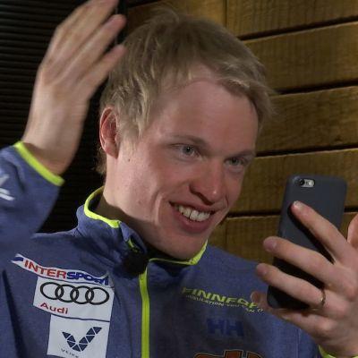 Iivo Niskanen kollar frisyren i mobiltelefonen.