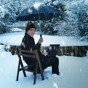 Hymyilevä mies istuu tuolilla lumihangessa läppäri sylissään ja sateenvarjo kädessään.