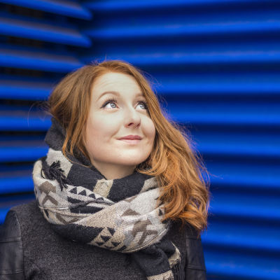 Tiia Ung seisoo sinisen seinän edessä ja katsoo yläviistoon.